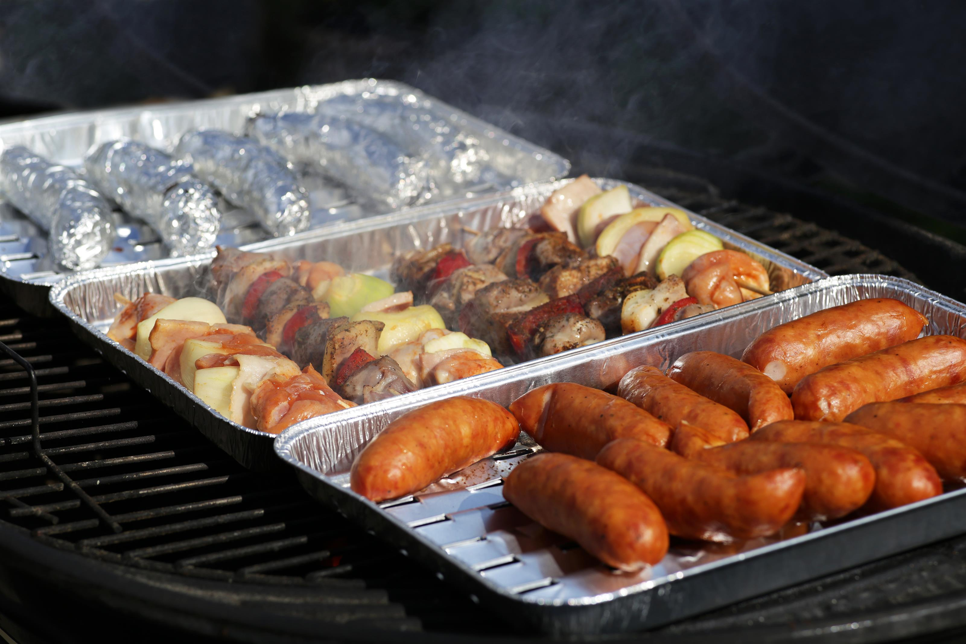 veggie and steak kabobs and sausages on disposable aluminum trays