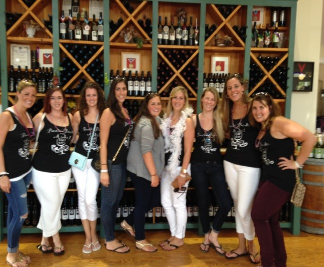 Women posing for photo in front of wine racks