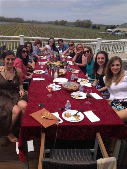 Women dining at outdoor table with vineyard in background