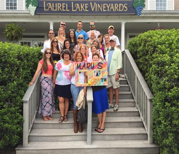 Group of people standing on steps in front of laurel lake vineyards sign