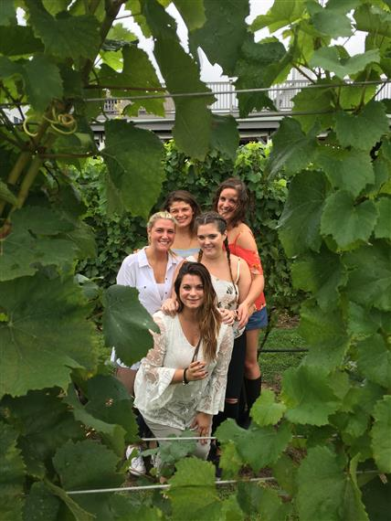 Group of people posing for a picture in a vineyard