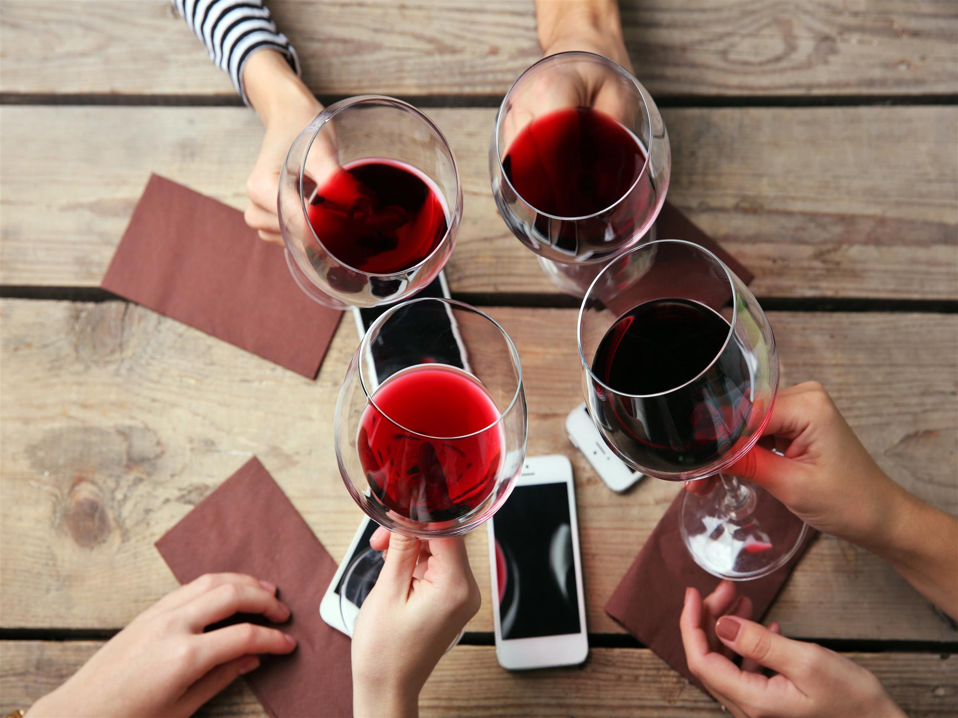 Glasses of red wine being held up over a wood table with napkins and a cell phone
