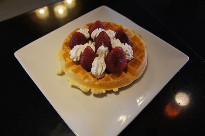 Waffle topped with whipped cream and strawberries