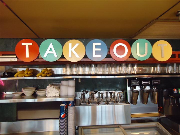 "Counter with cups and to go plates with a sign that reads ""TAKEOUT"""