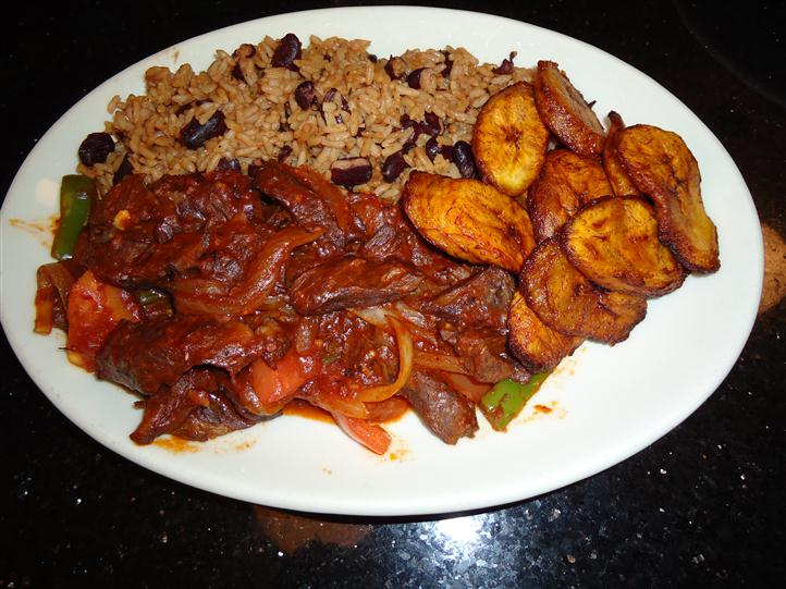 Stewed beef, Plantains, with rice and beans on a plate