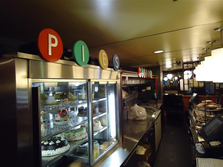"Restaurant counter with pastries and glass display that reads ""PIES"""
