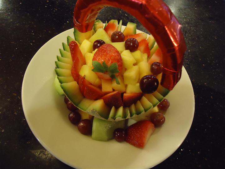 Fruit basket on a plate consisting of pineapples, grapes, strawberries, and honey dew