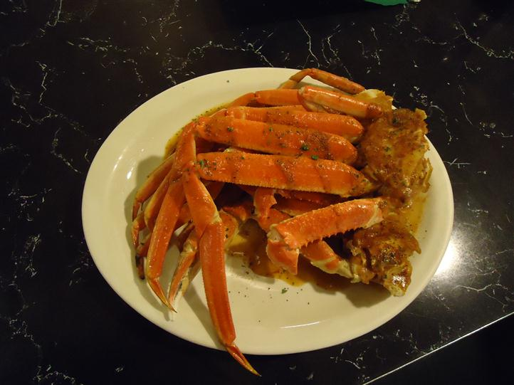 Crab legs on a plate with sauce on it