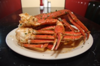 Crab legs glazed with garlic sauce on a plate.