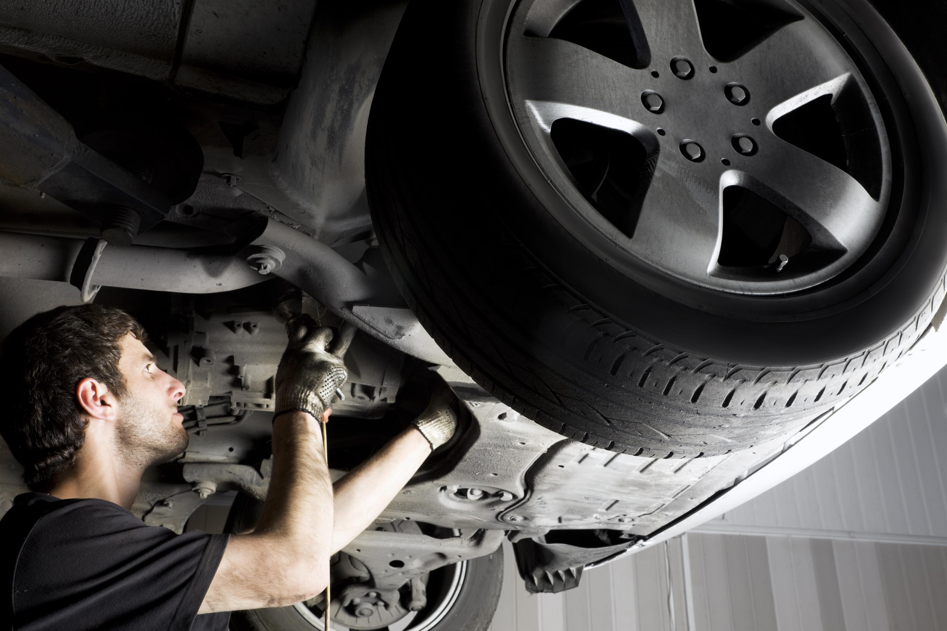 technician working on engine under a car
