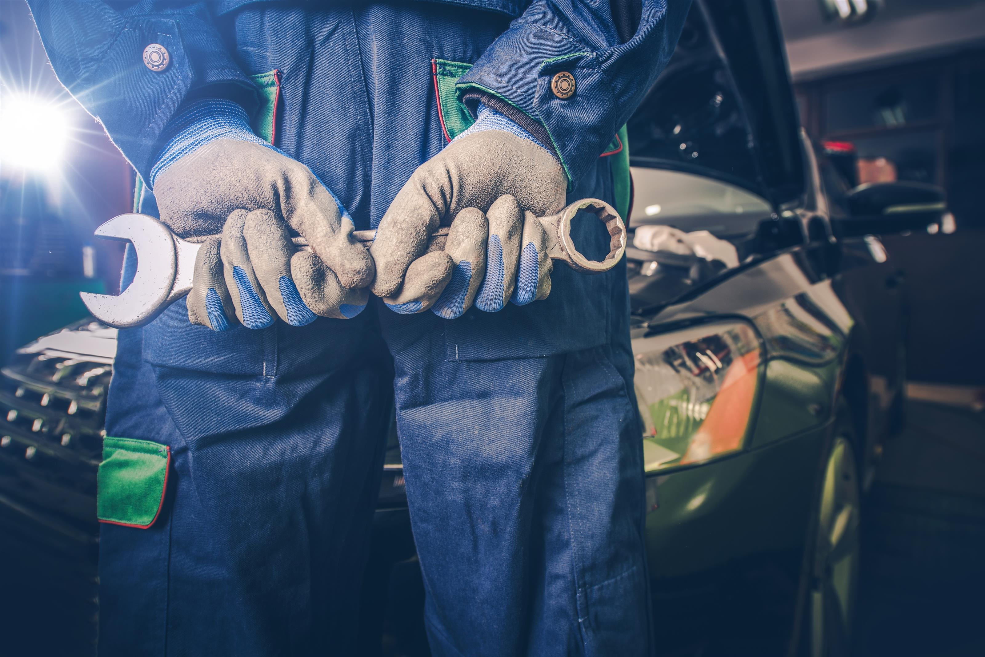 technician wearing gloves holding a wrench
