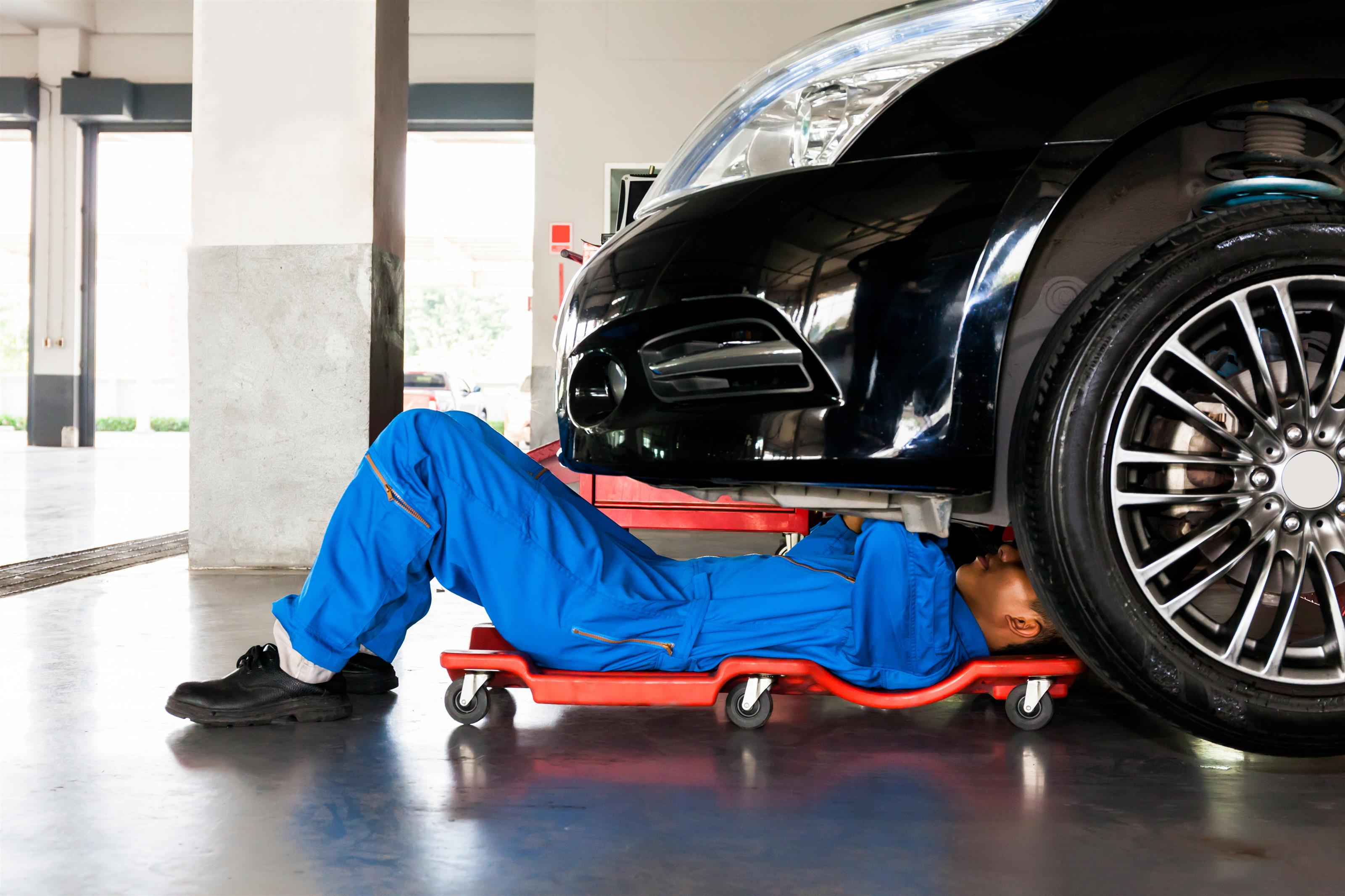mechanic on his back on a board with wheels under engine