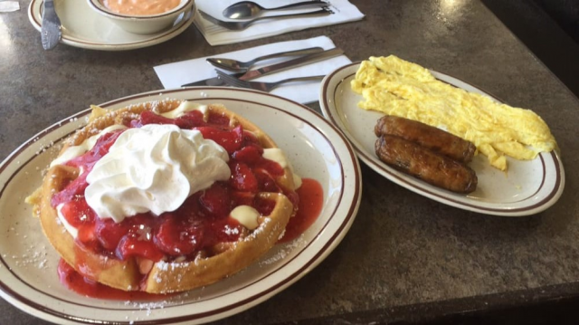 Waffle topped with straberry filling and whipped cream next to plate of scrambled eggs and sausage.