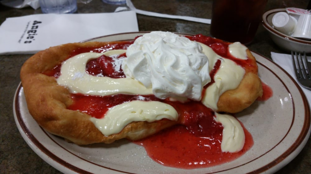 Cheesecake scone topped with delicious cheesecake batter, strawberry topping, whipped cream.