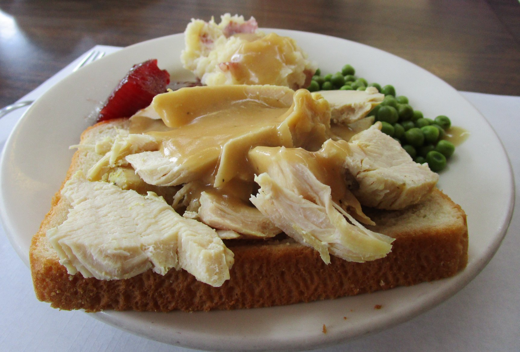 bread topped with turkey, turkey is covered in gravy with a side of english peas and mashed potatoes