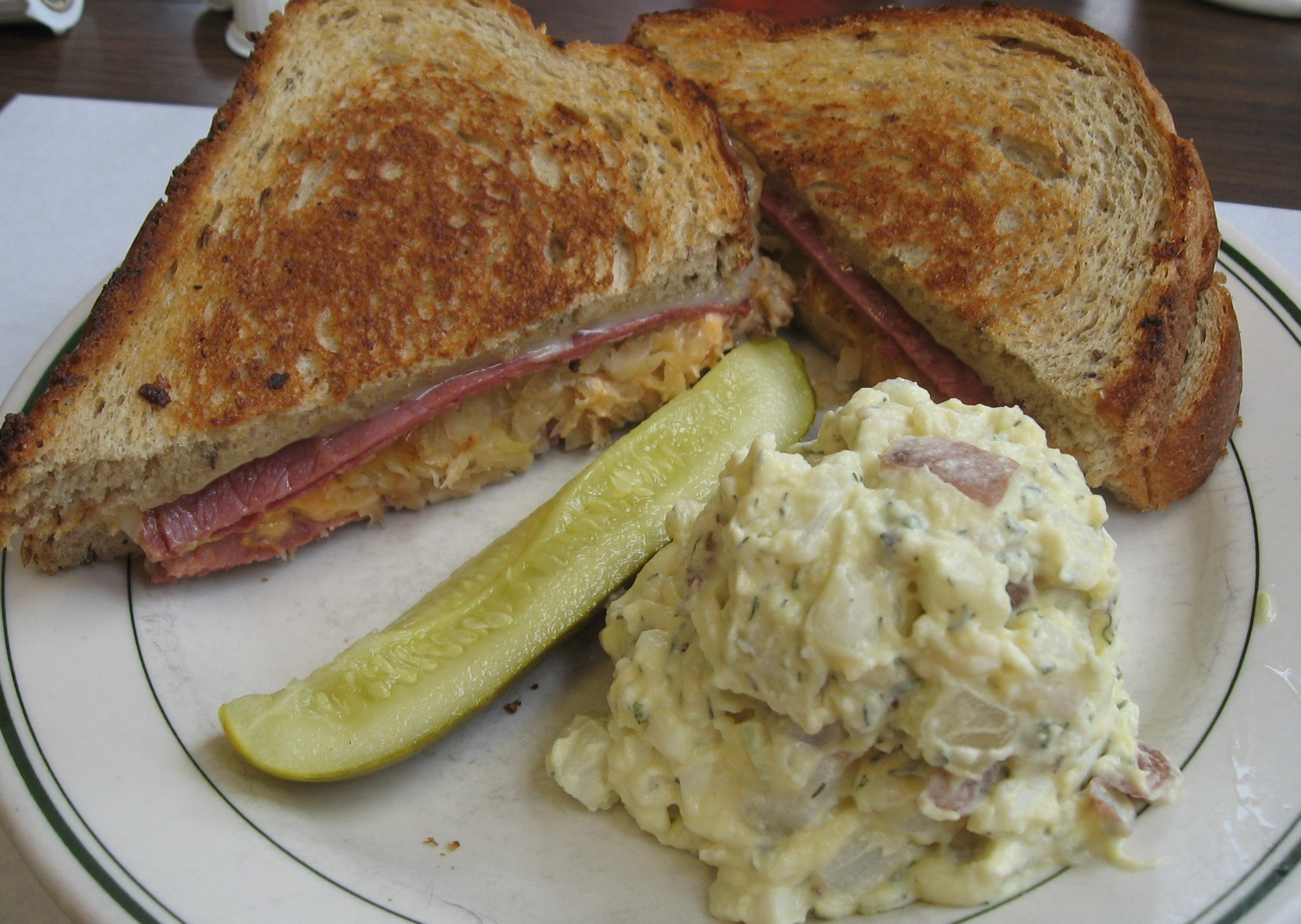sandwich on toasted bread with potato salad and a pickle