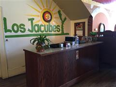 interior front desk with los jacubes logo on the wall