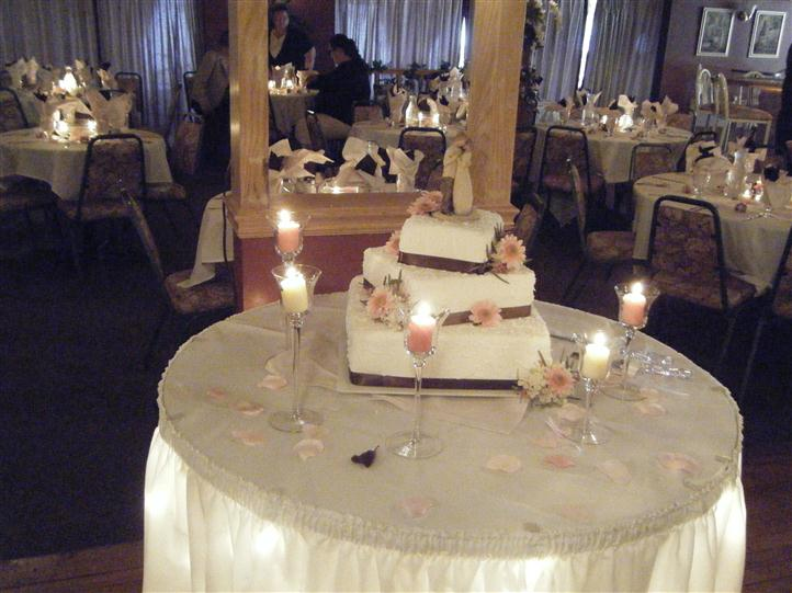 tables setup with napkins, utensils and candles with a large cake on one of the tables