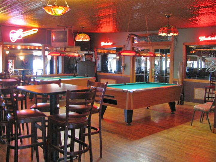 interior pool hall with two pool tables, tables and chairs