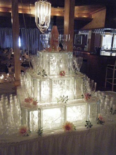 large 3 tier wedding cake surrounded by champagne glasses