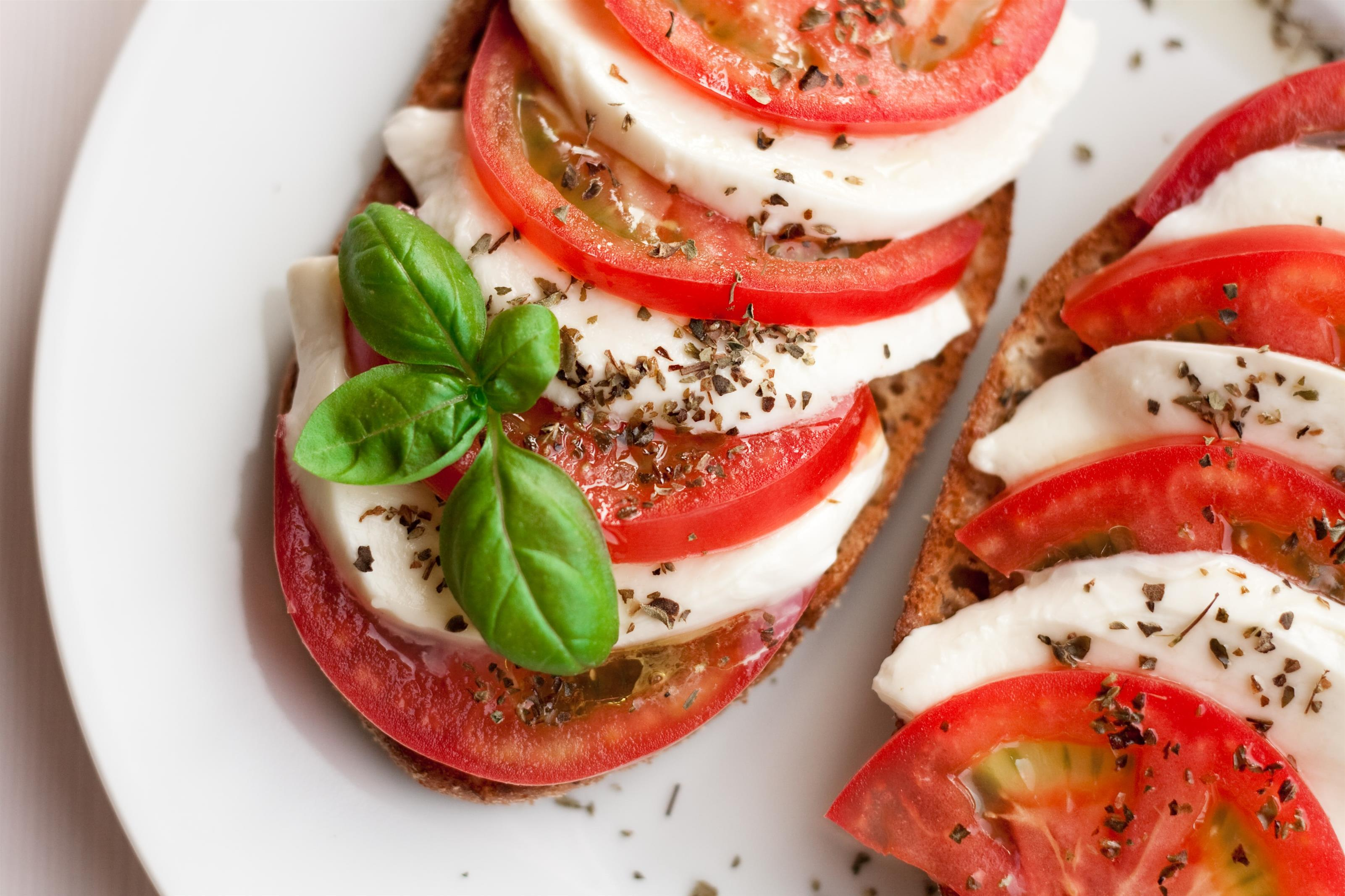 tomato mozzarella caprese topped with seasoning and basil leaf