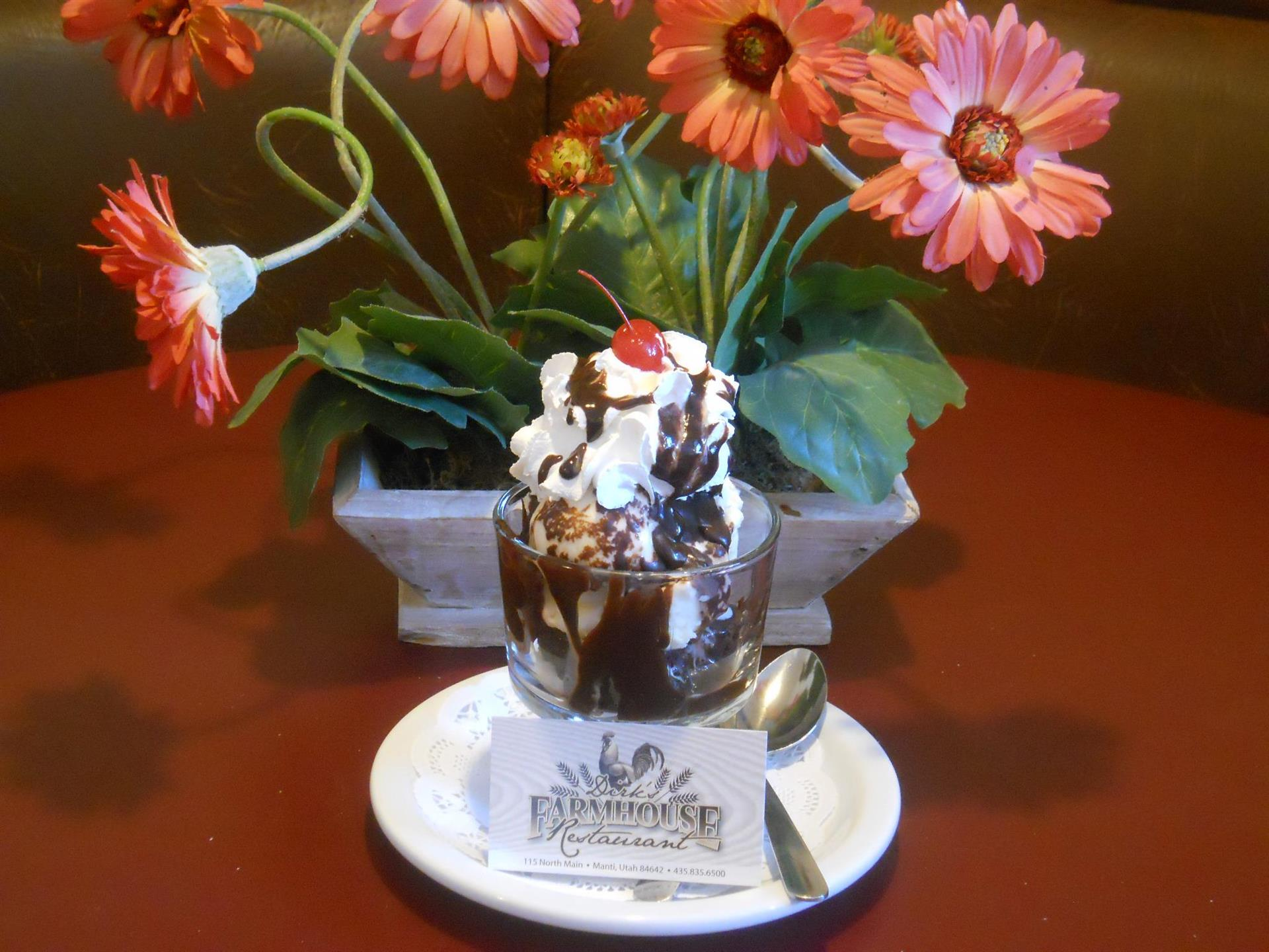 ice cream sundae in a cup with whipped cream, chocolate syrup and a cherry