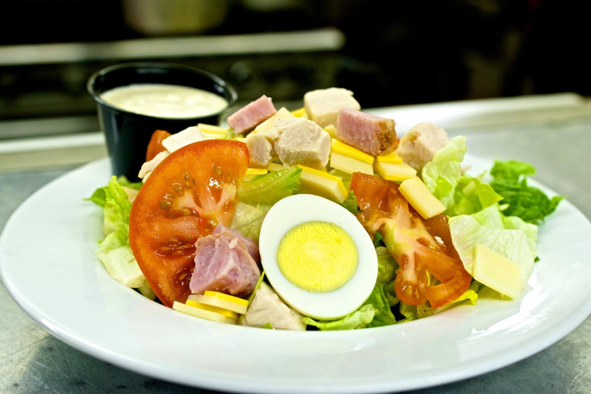 garden salad with lettuce, tomatoes, eggs, ham and cheese with a side of dressing