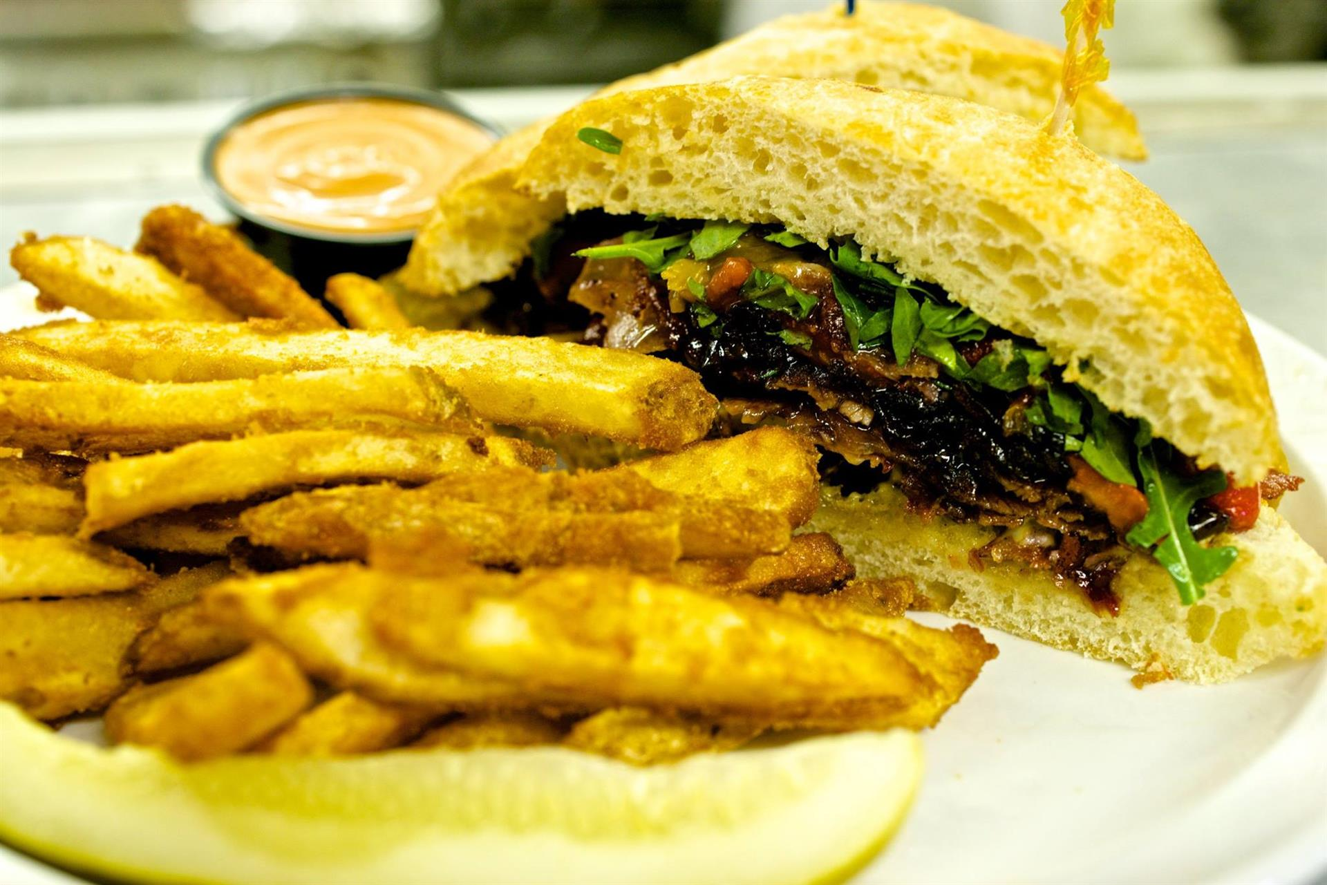 bbq sandwich with beef, lettuce, tomato and a side of french fries