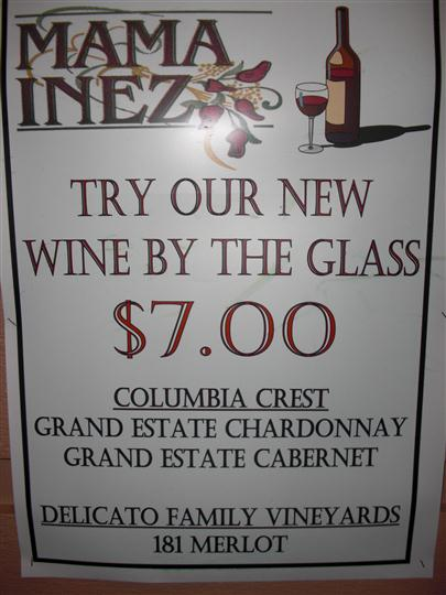 sign reads try our new wine by the glass $7.00 columbia crest grand estate chardonnay grand estate cabernet delicato family vineyards