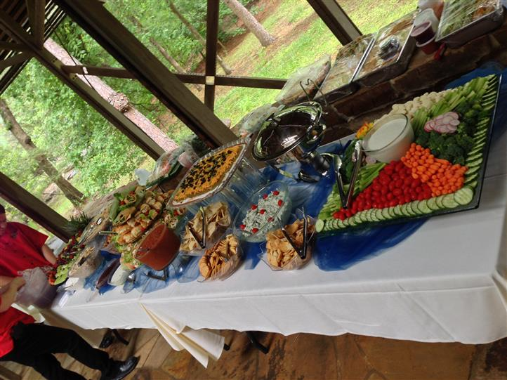 A buffet decorated in blue and white having several catering trays on it