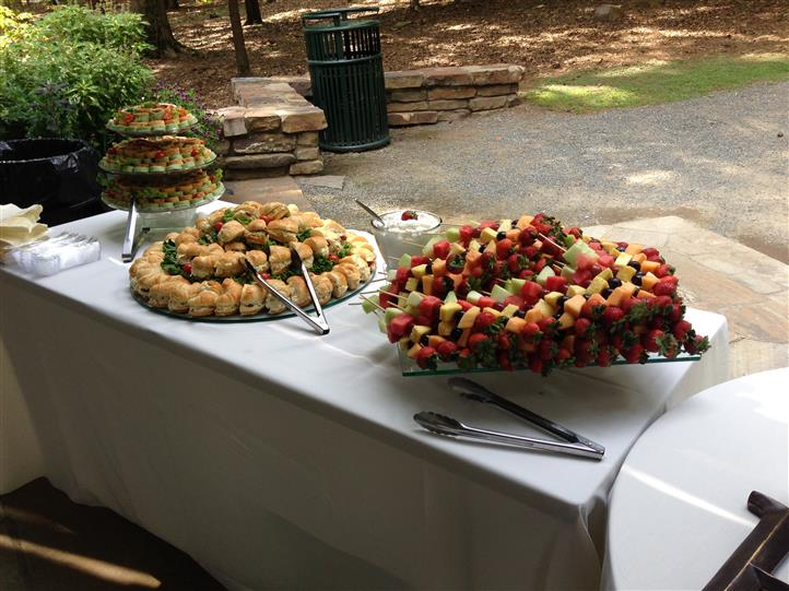 An outdoor buffet with several catering trays