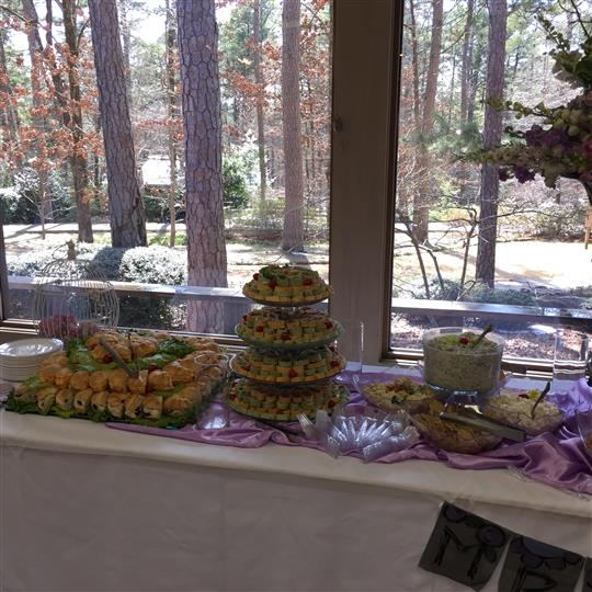 An interior buffet decorated in purple and white, with several catering trays