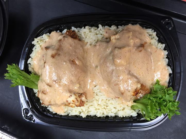 Α tray with two servings of chicken topped with sauce, over white rice