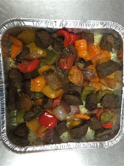 Roasted beef with colored peppers over white rice