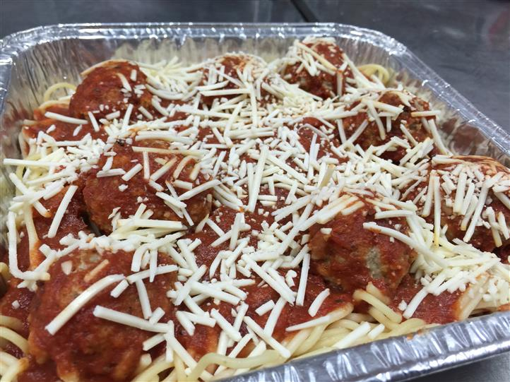 A tray of spaghetti with meatballs topped with shredded cheese
