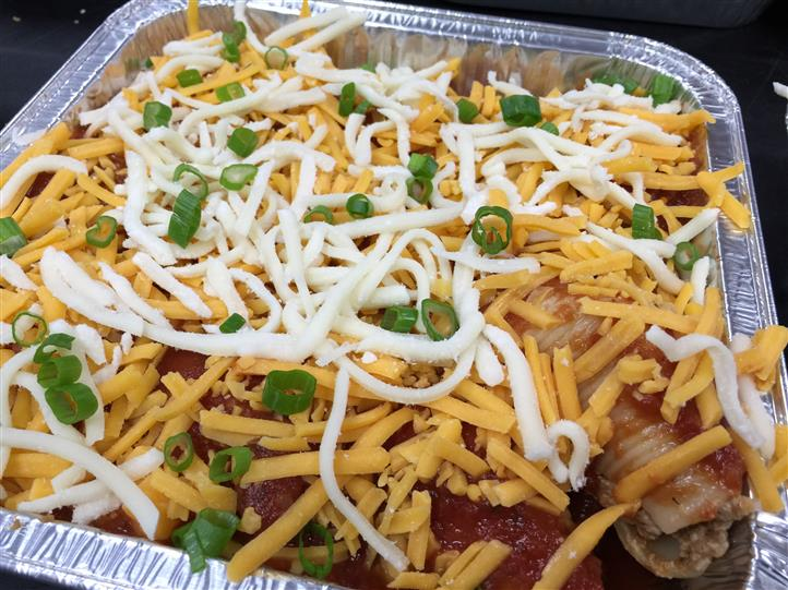 A tray of meat topped with shredded cheese