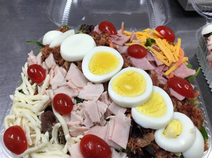 A tray of a salad topped with shredded cheese, eggs bacon and cherry tomatoes