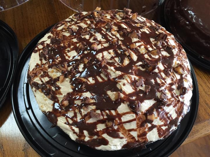 A cake topped with cream and chocolate syrup