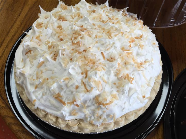 A cake topped with white cream and almonds