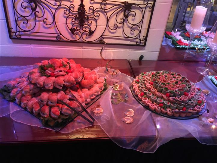 An interior buffet with a tray of mini sliders and a tray of wrap bites