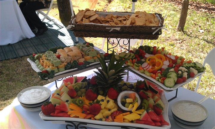 An outdoor shot of a buffet with a salad tray, a fruit salad tray, a cookies tray, and a wrap bites tray