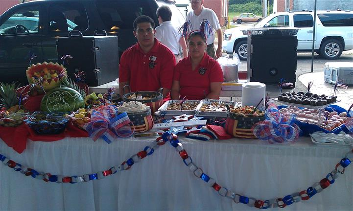 Two of our servers behind a decorated buffet