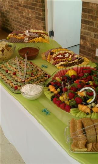 A decorated buffet with bites fruit salads, cold cuts and dipping sauces