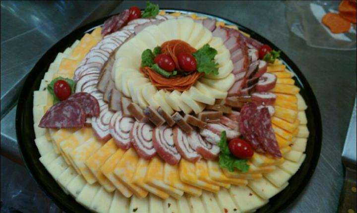 A decorated tray of cheese and cold cuts