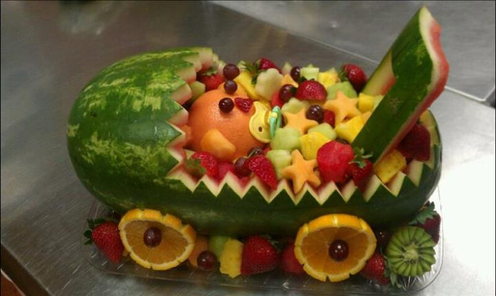 A sculpture of a stroller made from a watermelon, filled with several fruits