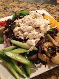 salad topped with cucumber slices, tuna salad and mushrooms