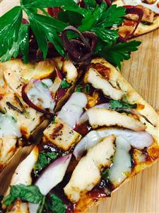 chicken flatbread pizza with bbq sauce and herbs