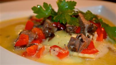 soup in a bowl with beef, tomatoes and herbs
