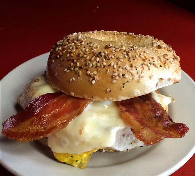 Bagel with eggs and bacon on white plate.