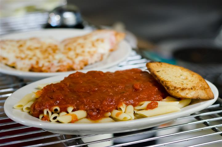 Pasta with meat sauce along with garlic bread.